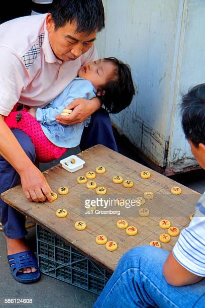Asian man playing xiangqi board game