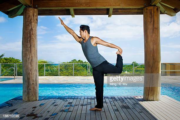 Asian man practicing yoga at poolside