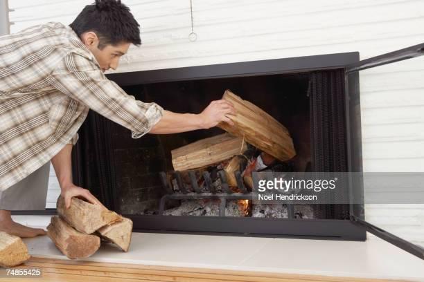Asian man putting logs in fireplace