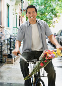 Asian man riding bicycle with flowers in basket