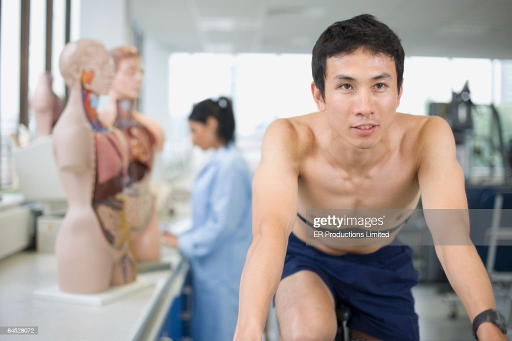 Asian man riding stationary bicycle in laboratory : Stock Photo