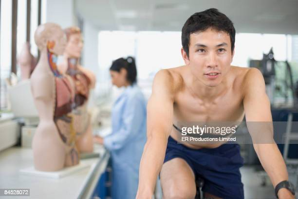 Asian man riding stationary bicycle in laboratory