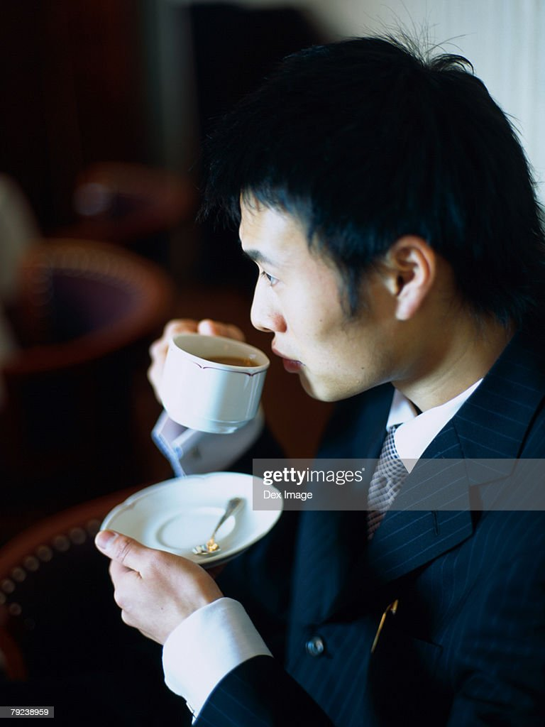 Asian Man sipping tea at a caf? : Stock Photo