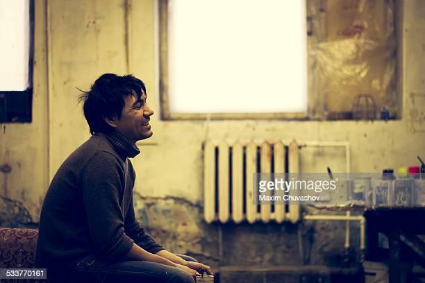 Asian man sitting in bedroom