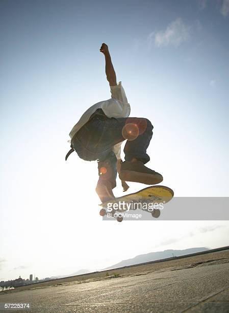 Asian man skateboarding and jumping