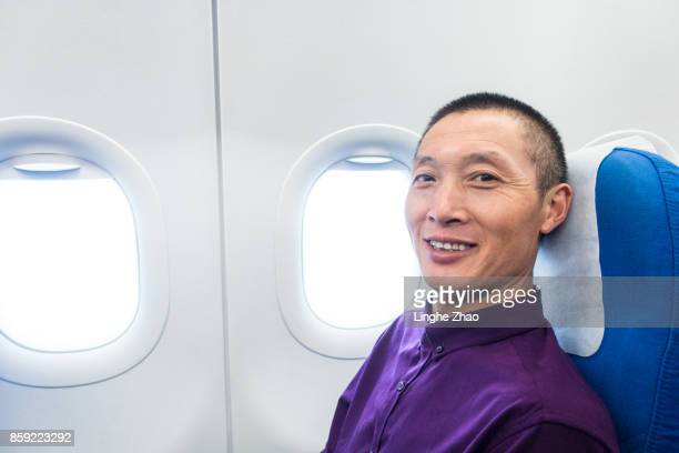 Asian man smiling at airplane