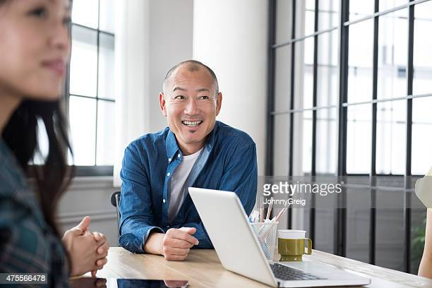 Asian man smiling in business meeting