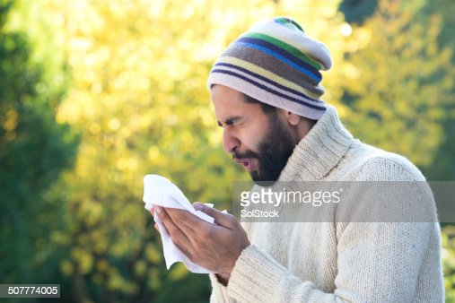 Asian Man Sneezing into Tissue