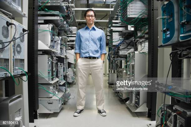 Asian man standing in computer server room