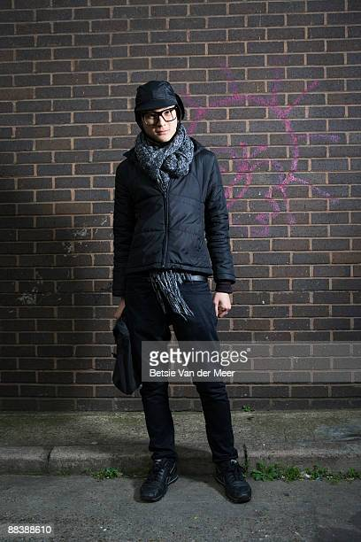 asian man standing in front of wall.