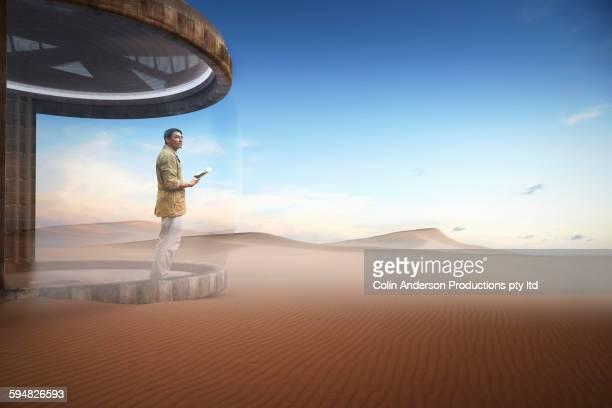 Asian man standing on patio in desert