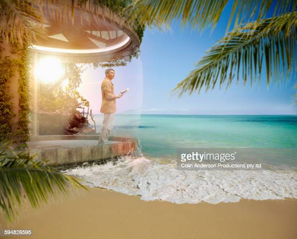 Asian man standing on patio on tropical beach