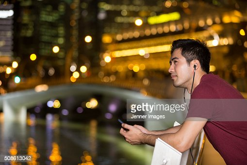 Asian Man standing outdoors with smart phone and earphones. : Stock Photo