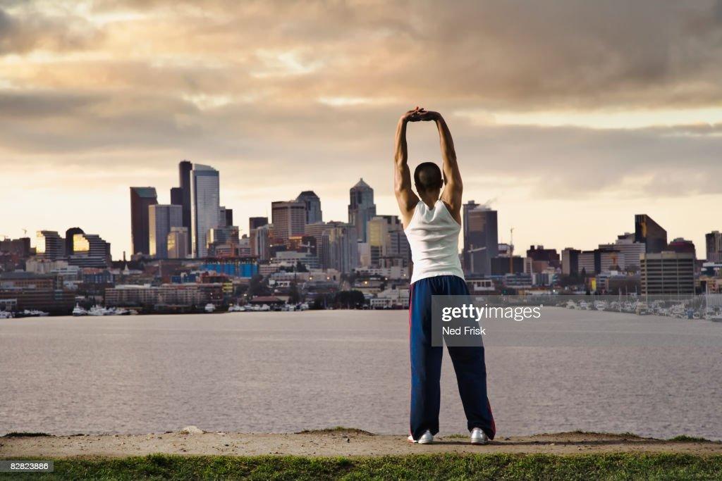 Asian man stretching at urban waterfront : Stock Photo