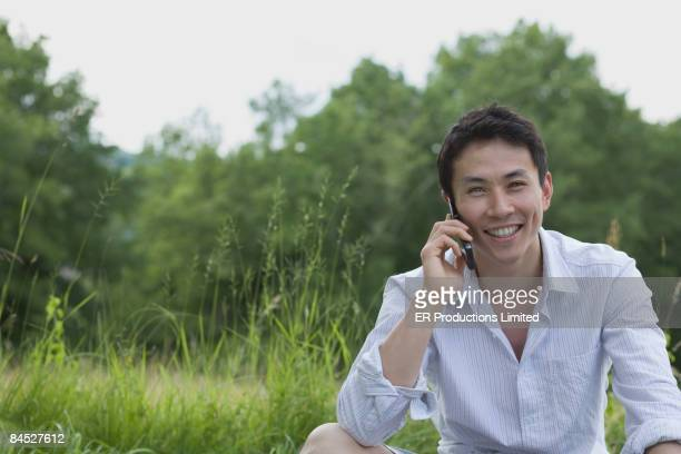 Asian man talking on cell phone outdoors