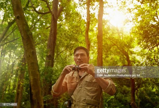Asian man using binoculars in jungle