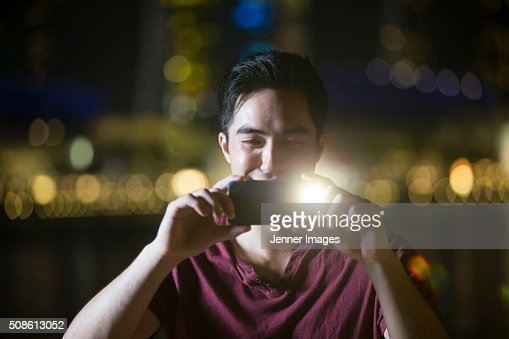 Asian man using his smart phone to take a photo at night. : Stock Photo