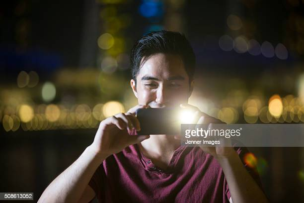 Asian man using his smart phone to take a photo at night.
