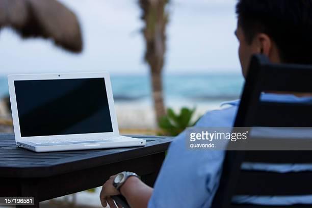 Asiatischen Mann mit Laptop am Strand, leeren Bildschirm