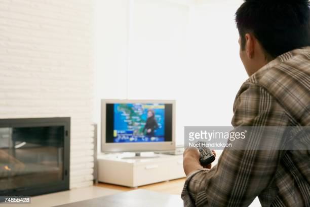 Asian man watching television