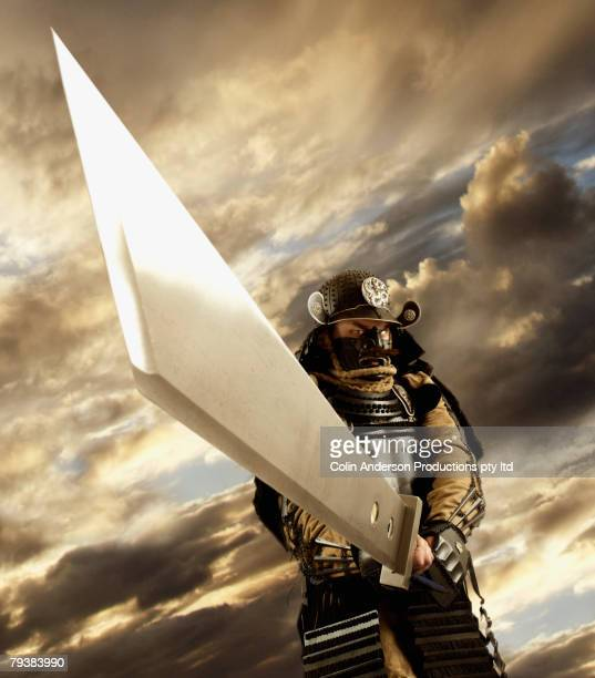 Asian man wearing samurai armor and holding sword