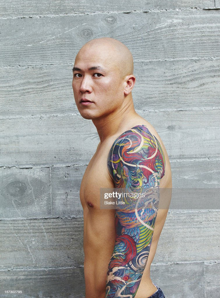 Asian man with arm tattoo. : Stock Photo