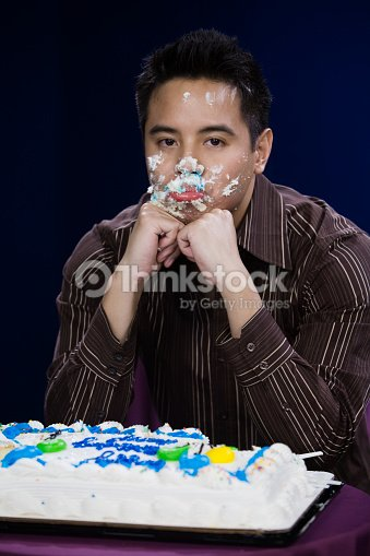 Asian Man With Birthday Cake On Face Stock Foto