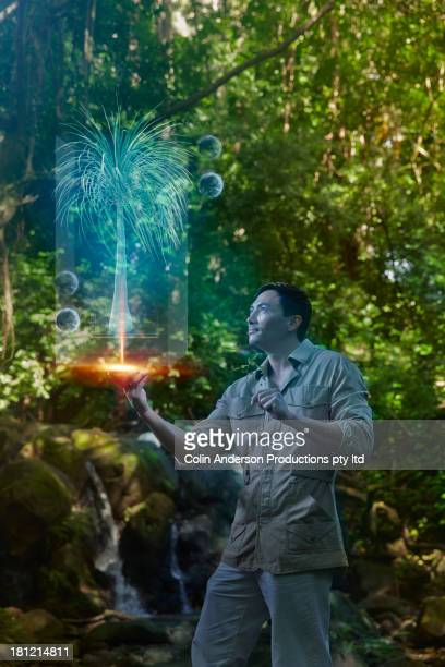 Asian man with computer screen projection in jungle