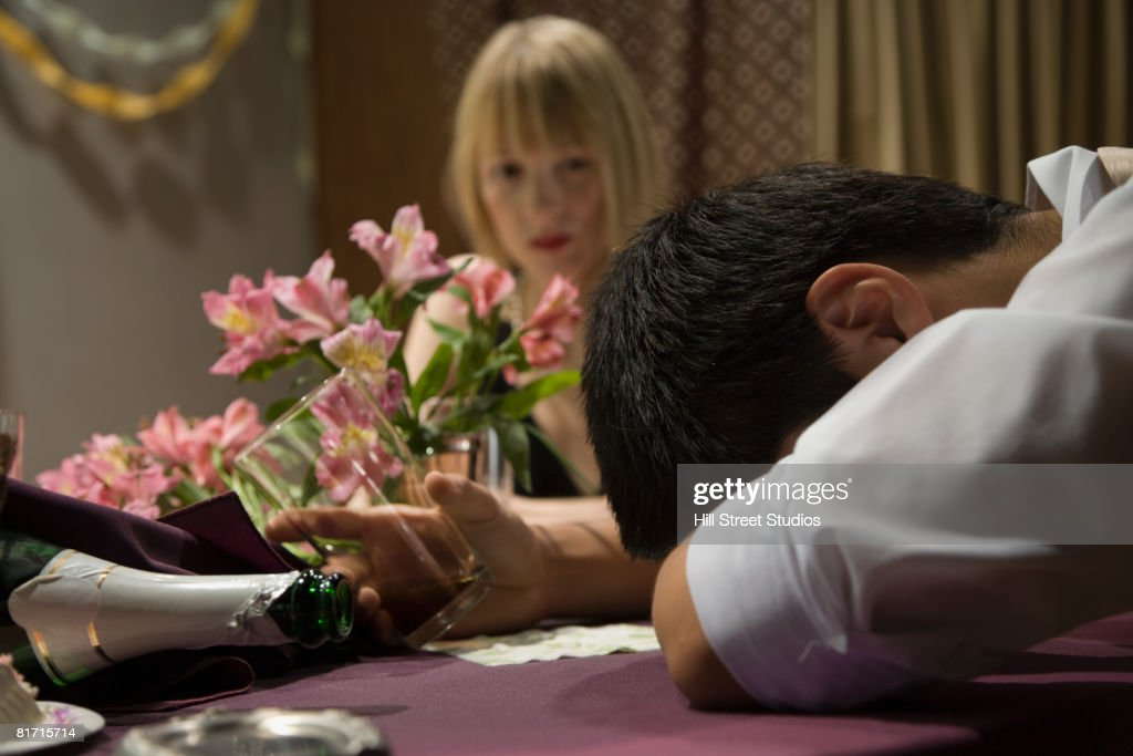 Asian man with head on table : Stock Photo