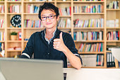 Young adult Asian man with laptop, thumbs up ok sign, home office or library scene, bookshelf with clock blur background with copy space, success or technology concept