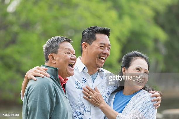 Asian man with senior parents in park