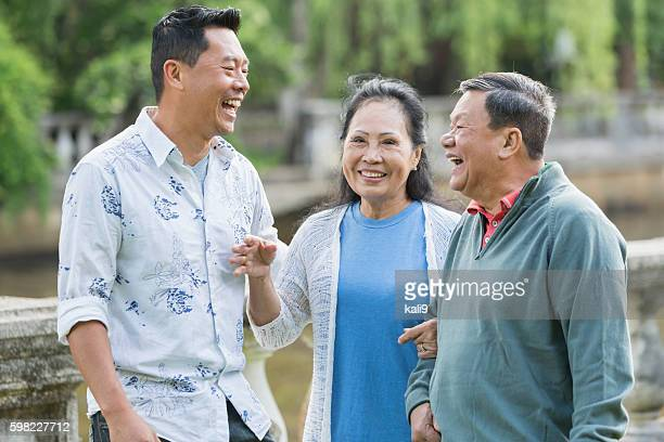 Asian man with senior parents in park walking, laughing