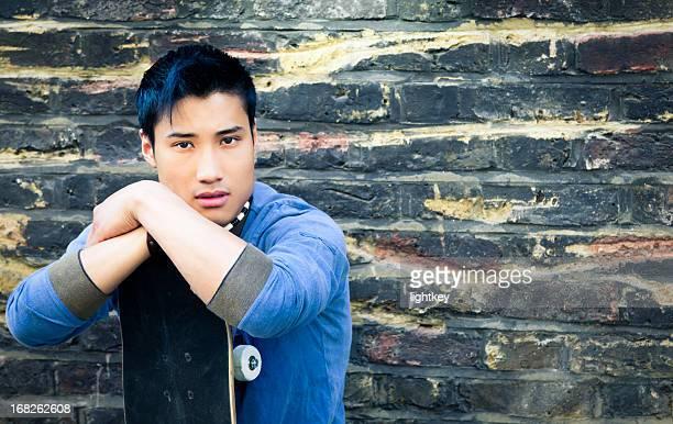 Asian man with skateboard
