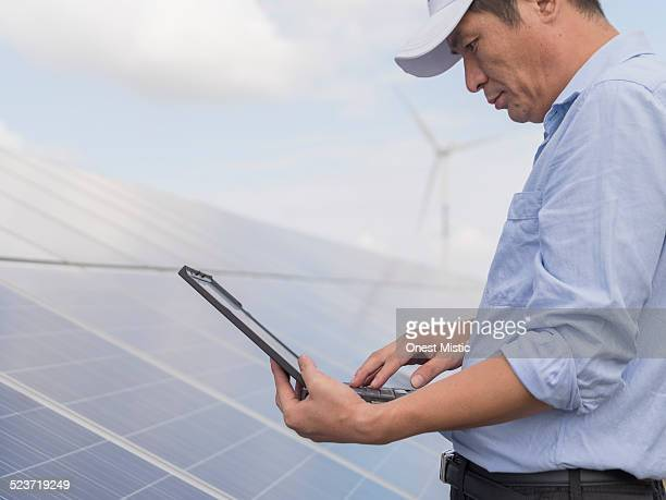 asian man working on laptop in solar plant