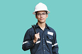 Asian man,Engineer or Technician in white helmet, glasses and blue working shirt suit holding wrench, isolated on green, mechanic and Oil and Gas industrial concept with clipping path.