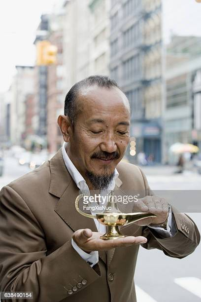 Asian mature man rubbing genie lamp in downtown city