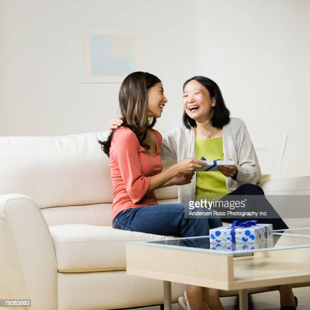 Asian mother and adult daughter exchanging gift