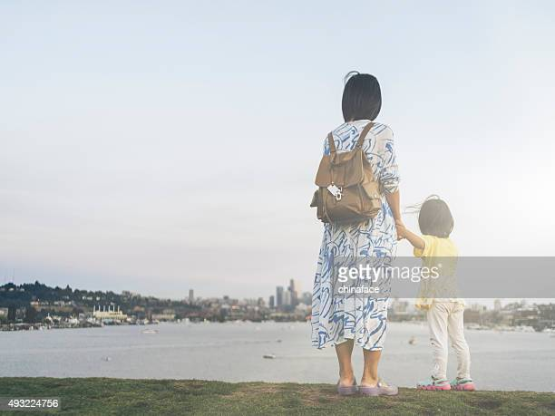 asian mother and daughter looking at skyline of seattle