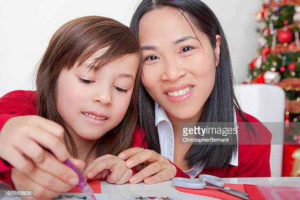 Asian mother and daughter making christmas cards