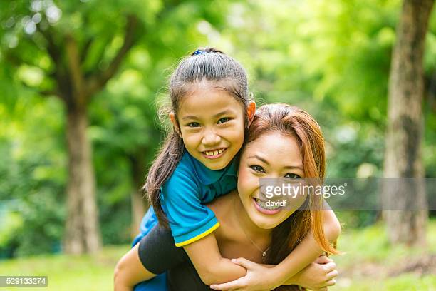 Asian Mother and Daughter Piggybacking Together in the Park
