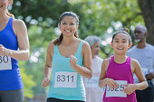 Asian mother and daughter run together in a marathon. They are smiling.  They are in a public park on a sunny day.