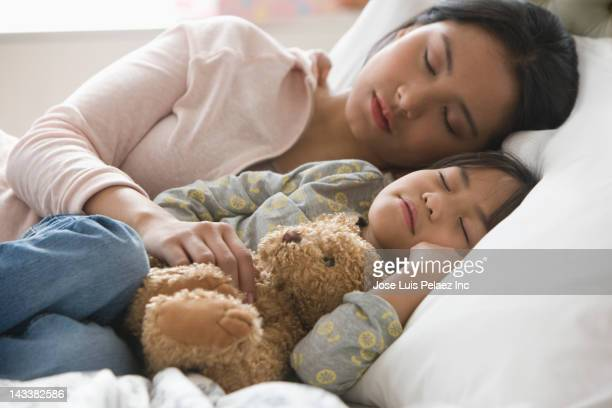 Asian mother and daughter sleeping in bed