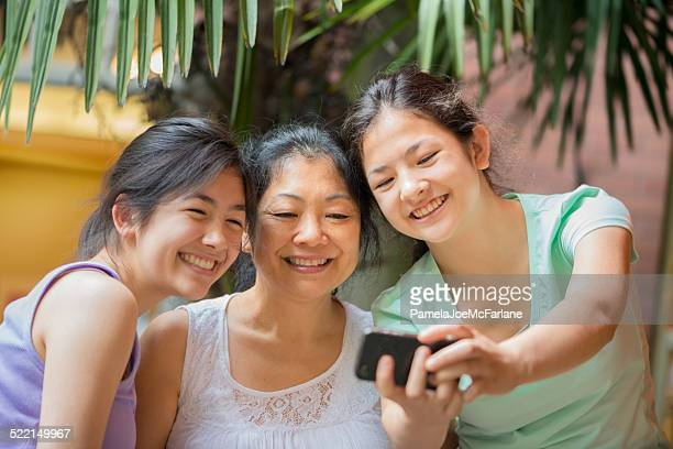 Asian Mother and Eurasian Daughters Taking Selfie on Tropical Vacation