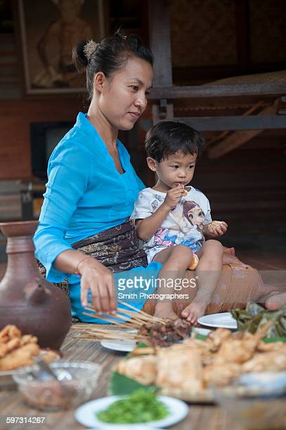 Asian mother and son eating on woven mat