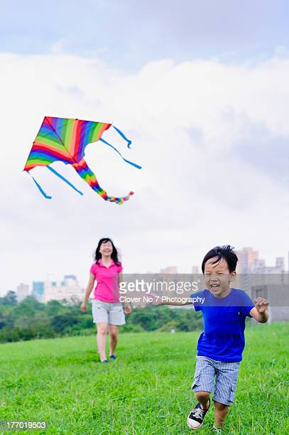 Asian mother and son fly a kite.