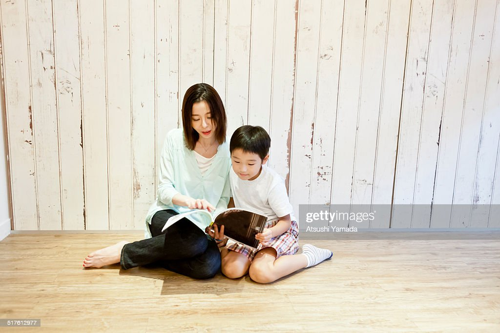 Asian mother and son reading magazine