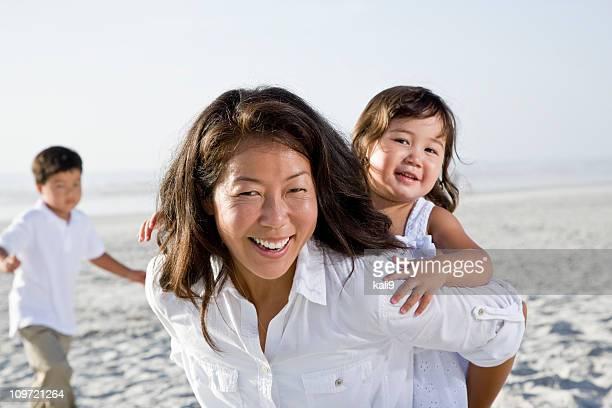 アジアの母と 2 つの小さな子供のビーチ