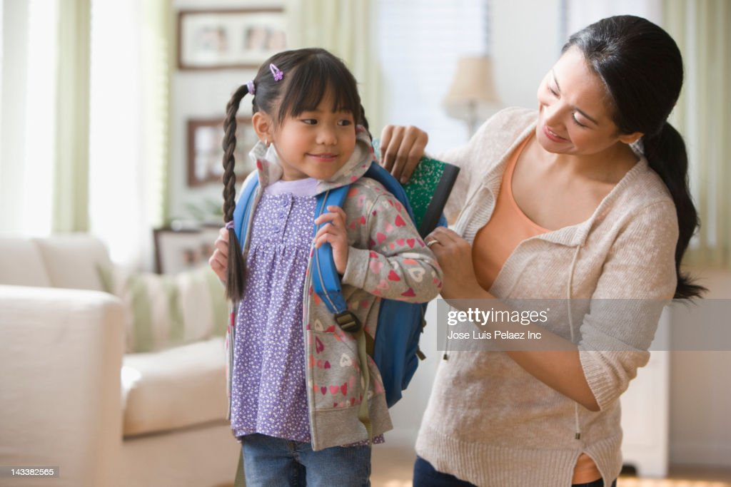 Asian mother helping daughter get ready for school : Stock Photo