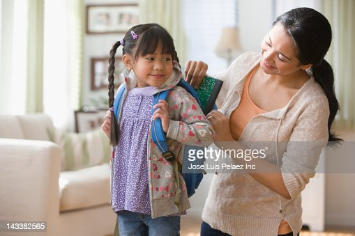Asian mother helping daughter get ready for school : Stockfoto