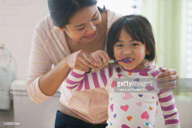 Asian mother helping daughter to brush her teeth